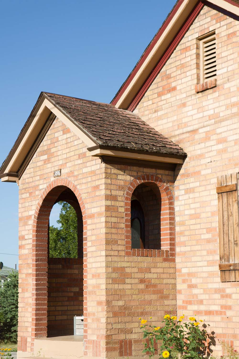 The front of a brick home with an arched entryway.