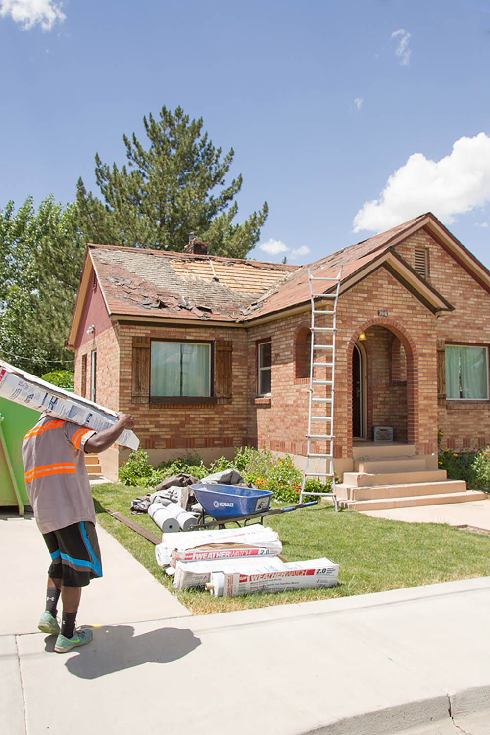 A man walks in front of a brick home having the roof replaced.