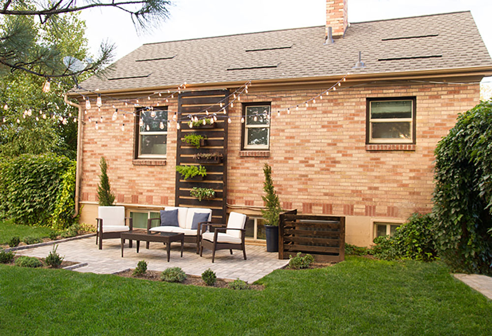 The backyard of a brick home decorated with dark wood patio furniture.