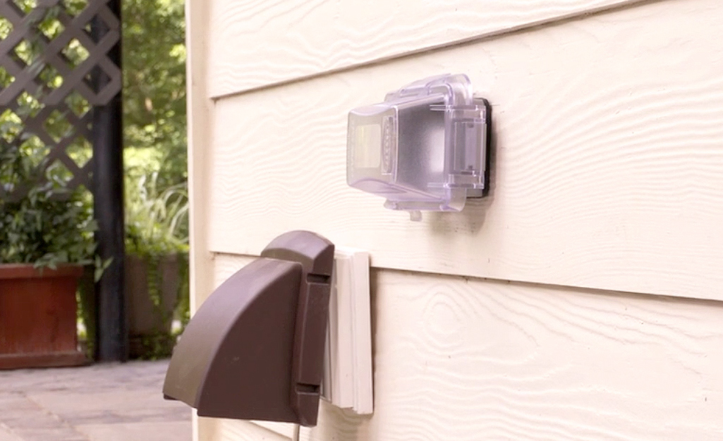 A covered outdoor outlet on the side of a house.