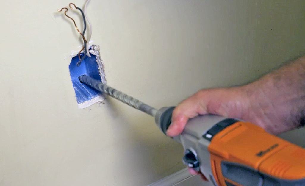 A person using a long drill bit to drill through the back of an interior outlet box.