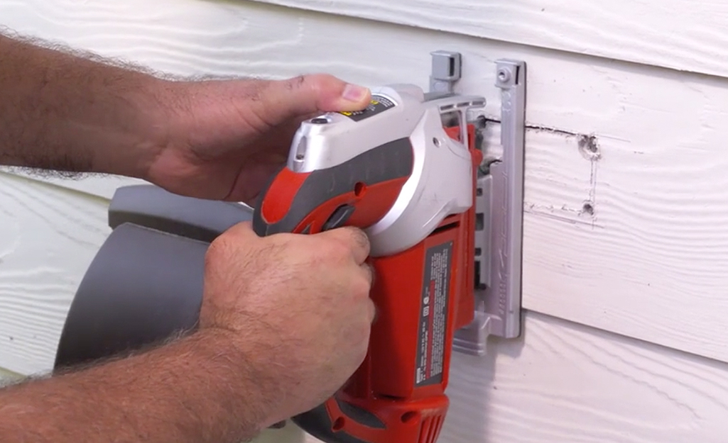 Someone using a saber saw to cut out a hole in a home's exterior siding.