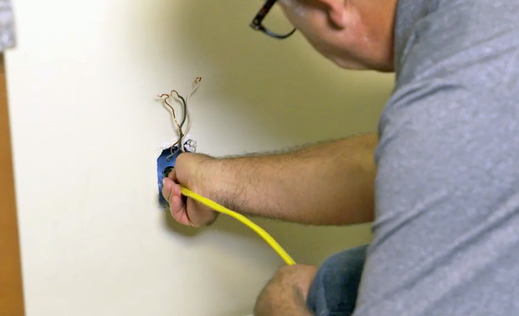 A person running cable through an outlet electrical box.