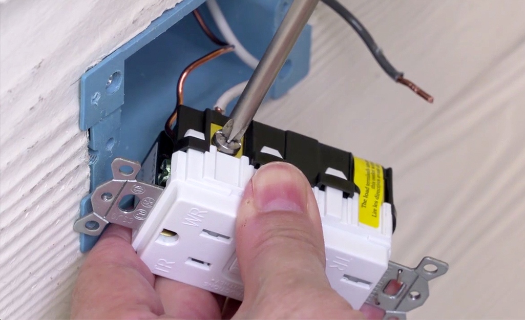 A person screwing a wire connection to a GFCI outlet.