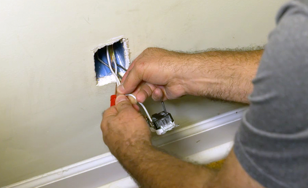 A person connecting several white wires to an indoor outlet.