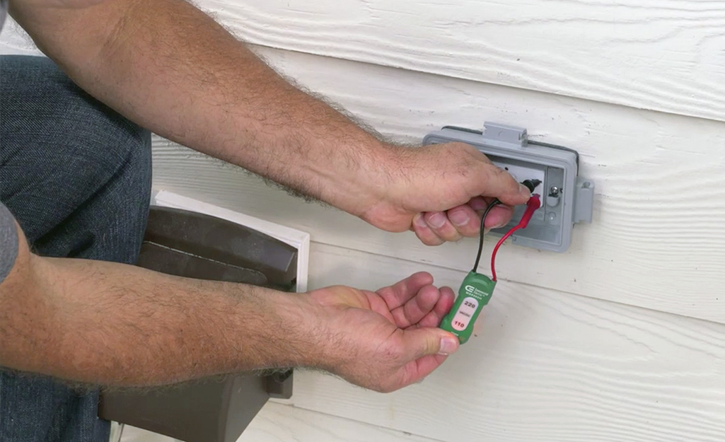 A person testing an outdoor outlet with a voltage tester.