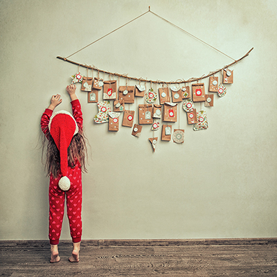 A child in a Santa hat and red pajamas reaching for a Advent calendar bag.
