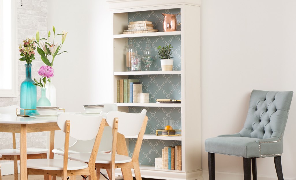 A bookshelf with wallpapered back panels.