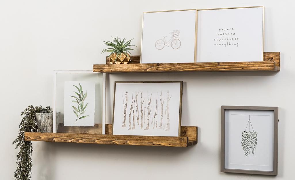 Succulent plants and minimalist art prints sit on wood floating shelves.