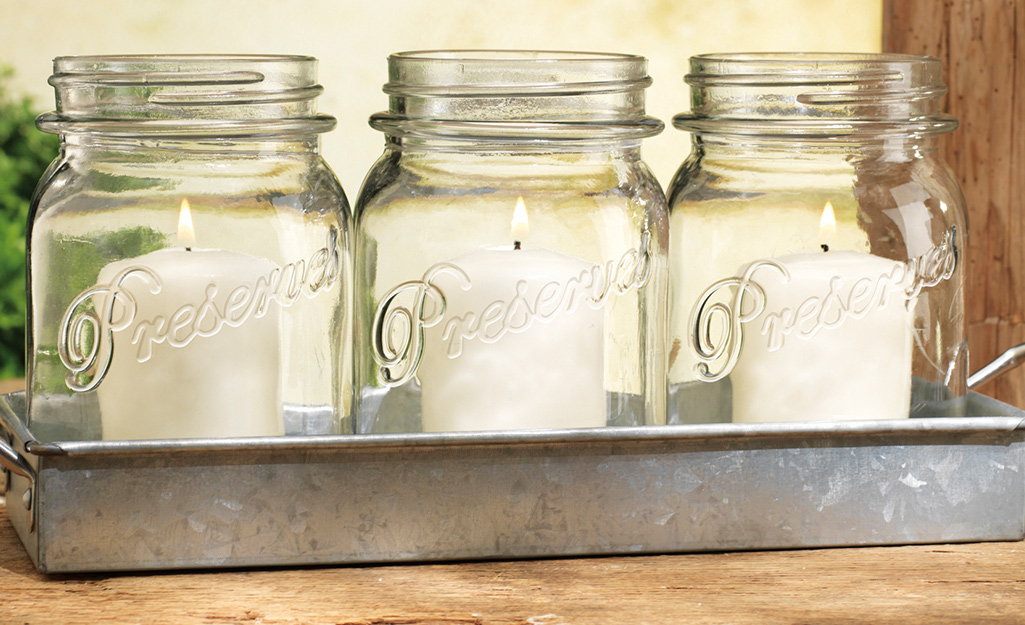 Three mason jars that have been repurposed as home decor candle holders.
