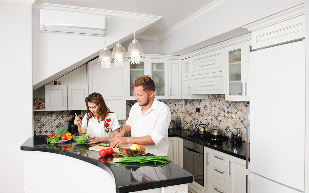 Two people in a kitchen with a built-in air conditioner.
