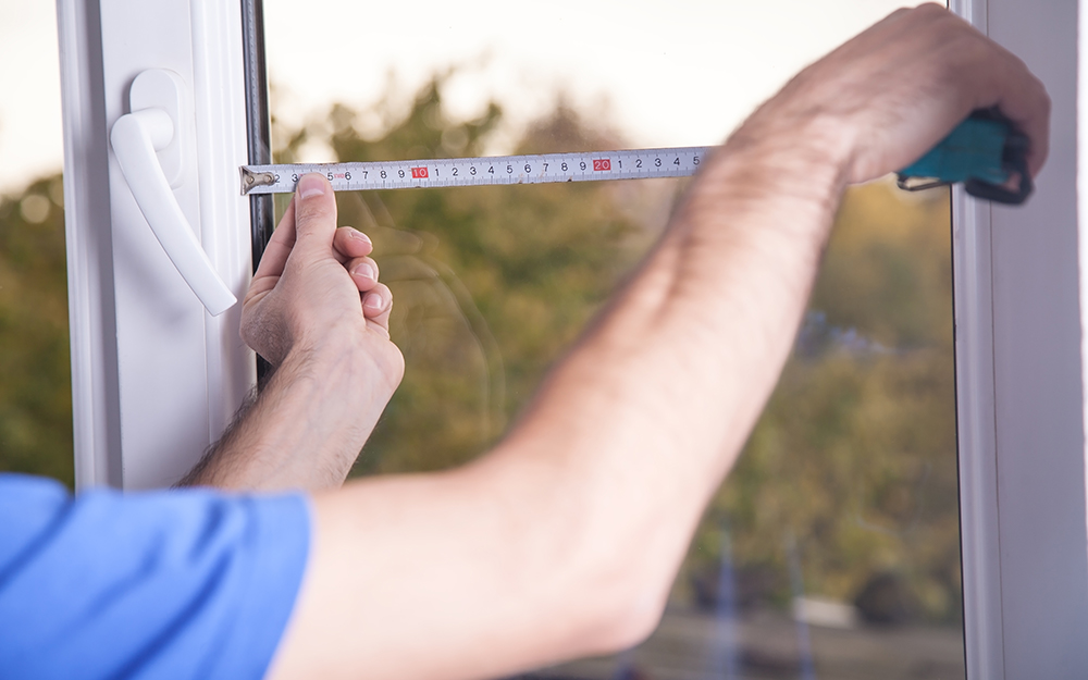 A person measuring a window with a tape measure.