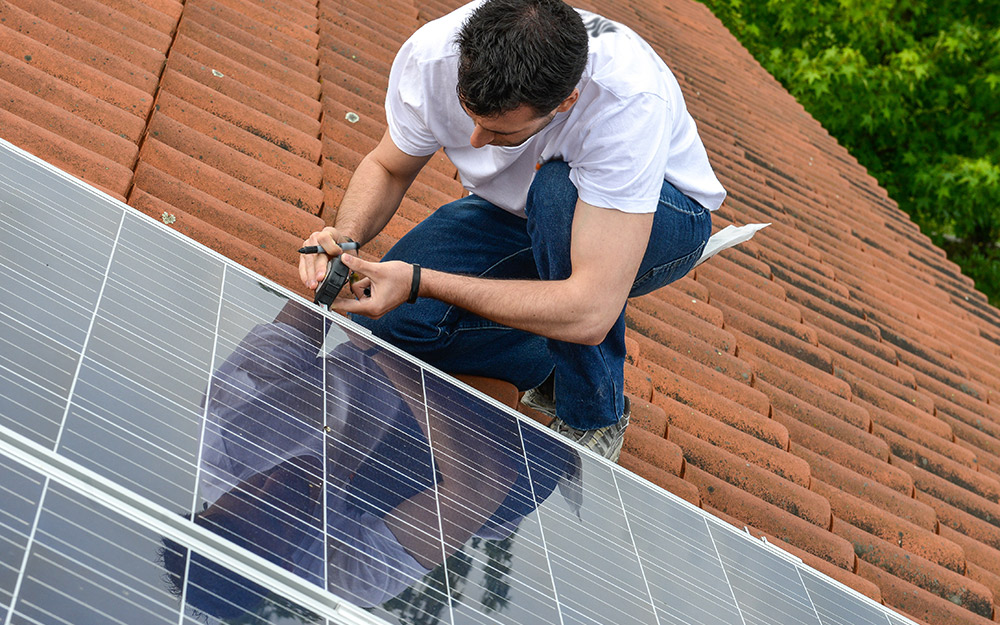 A person installing solar panels on the roof of a home
