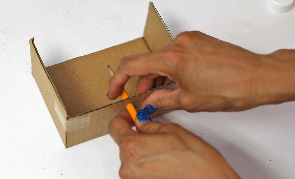 Dùng bút chì tạo một lỗ trên bìa cứng.
