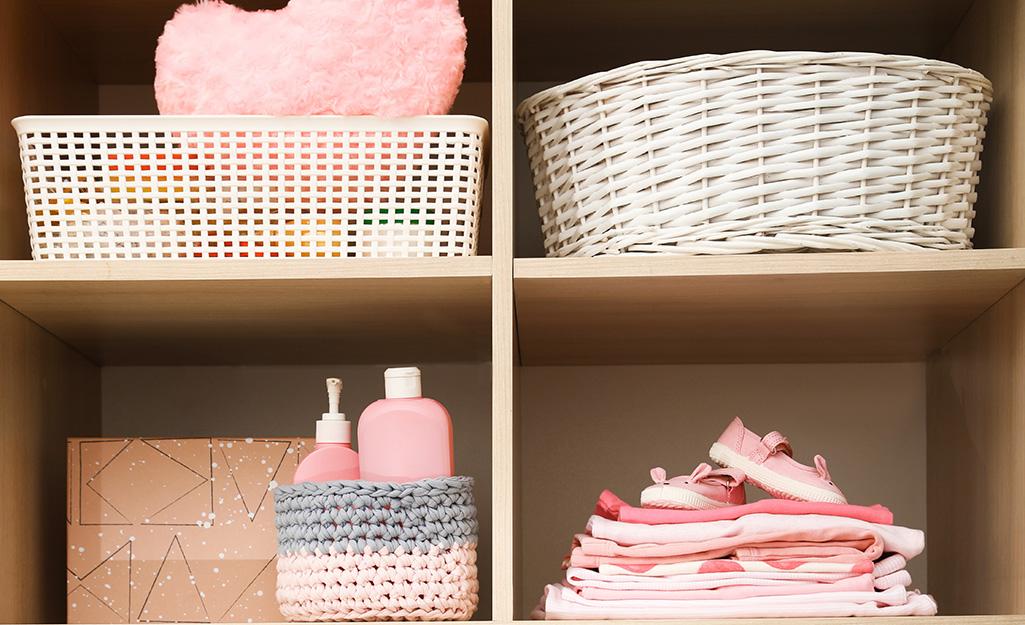 Various storage bins sit on a closet shelf in a baby's closet.