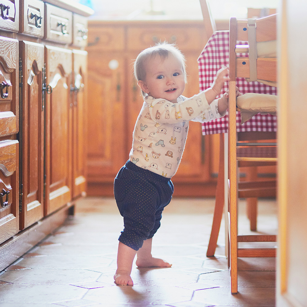A baby holding a chair in a kitchen.