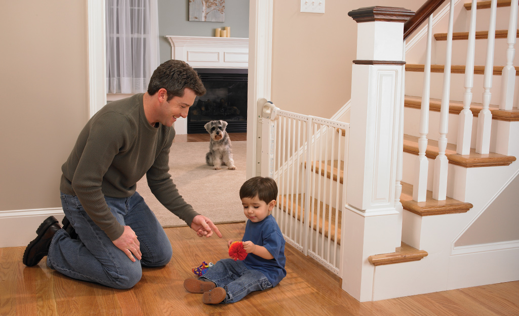 A dad and toddler sit in front of a baby gate that's attached to a staircase.