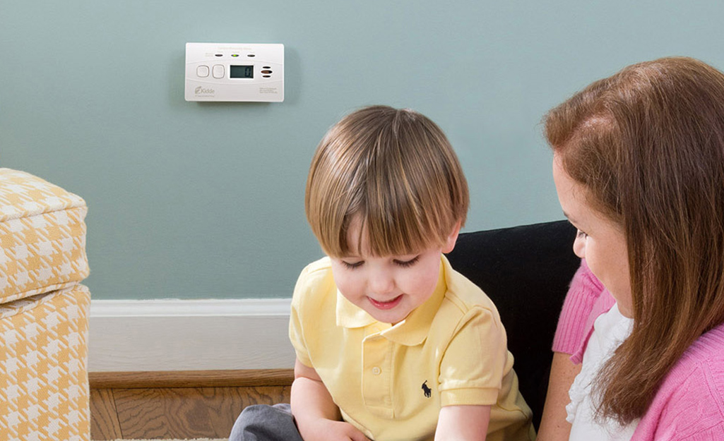 A carbon monoxide detector installed on a wall in a playroom.