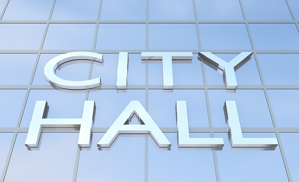 A glass building with city hall on it.