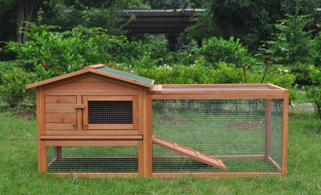 A wood chicken coop in a yard.