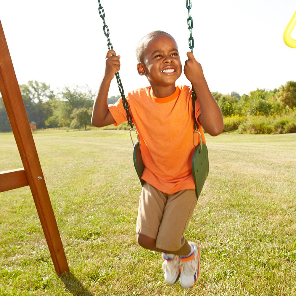 A boy swings on a swing set.