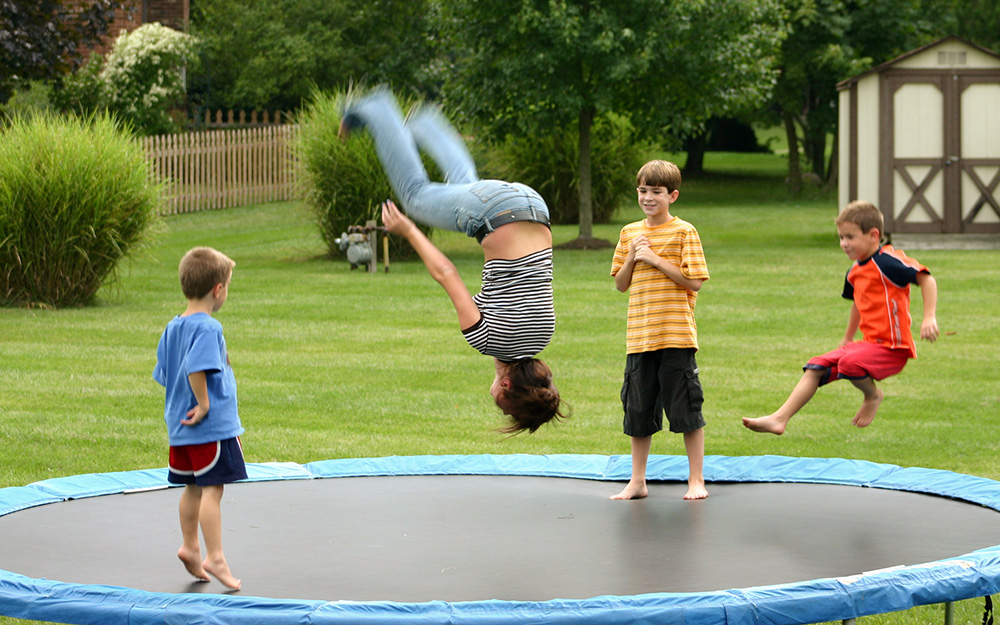 Children playing on a trampoline.