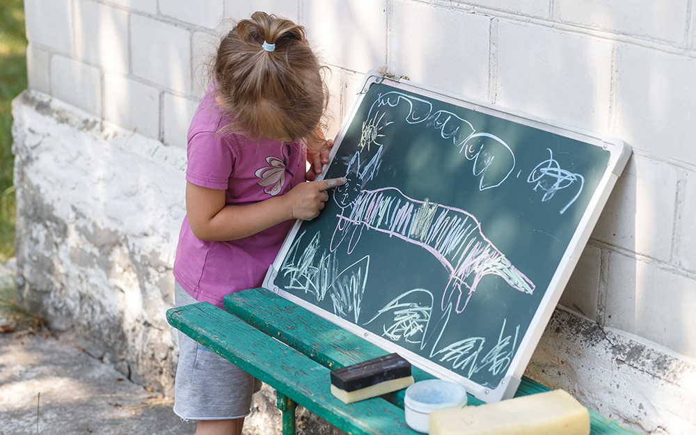 A child drawing on a chalkboard.