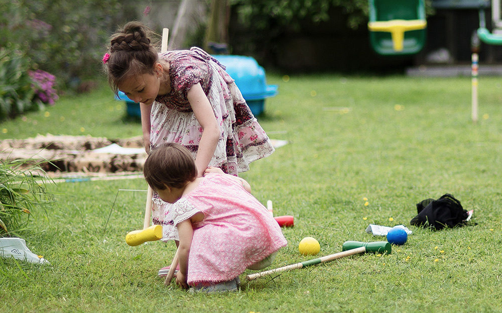 Children playing with a croquet set.