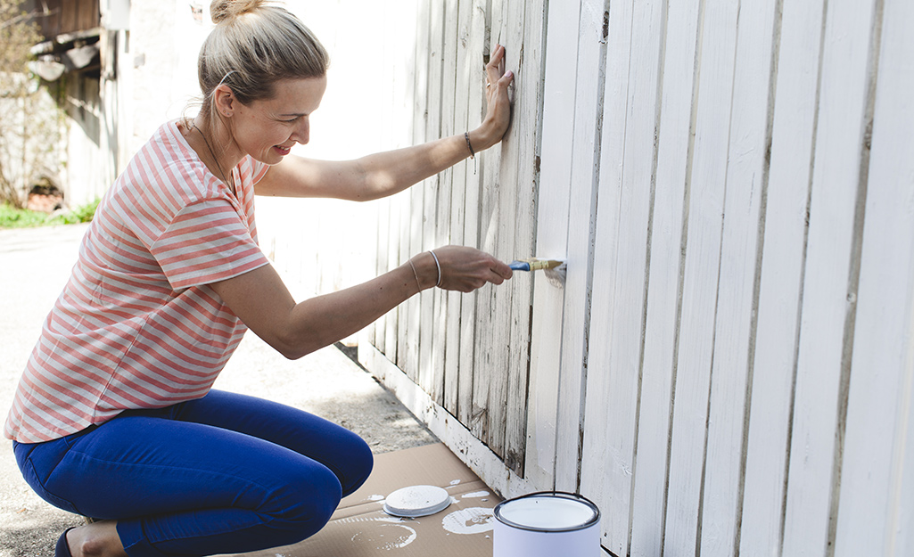 A woman painting a worn fence with a fresh coat of white paint.