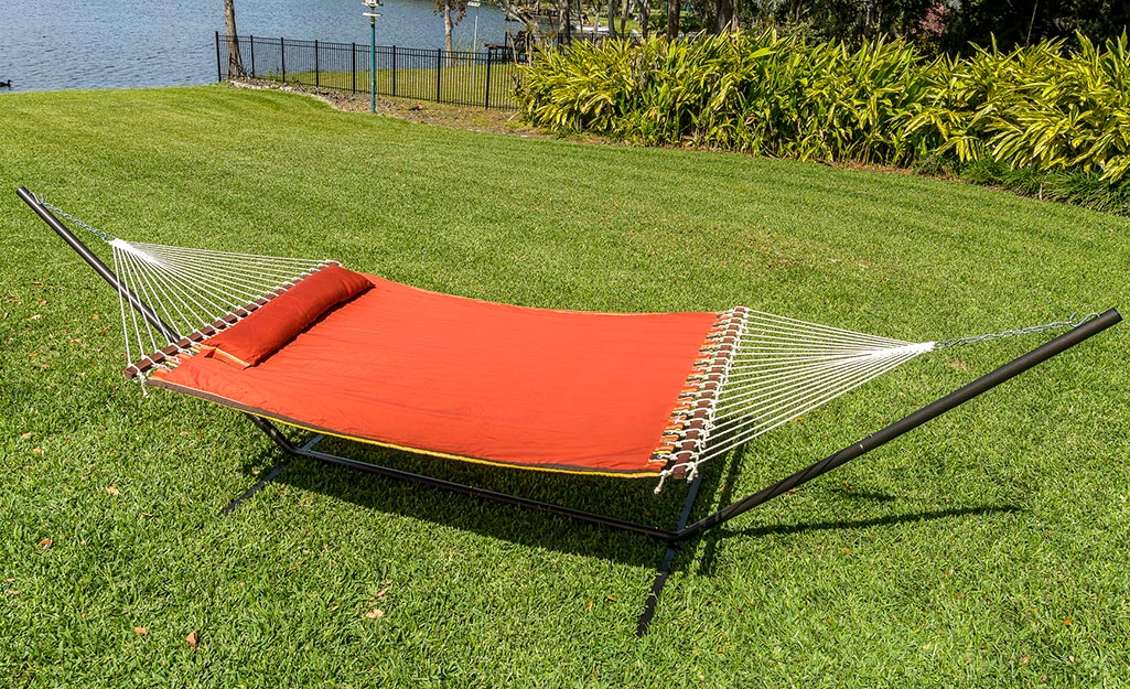 A red hammock on a stand in a backyard.