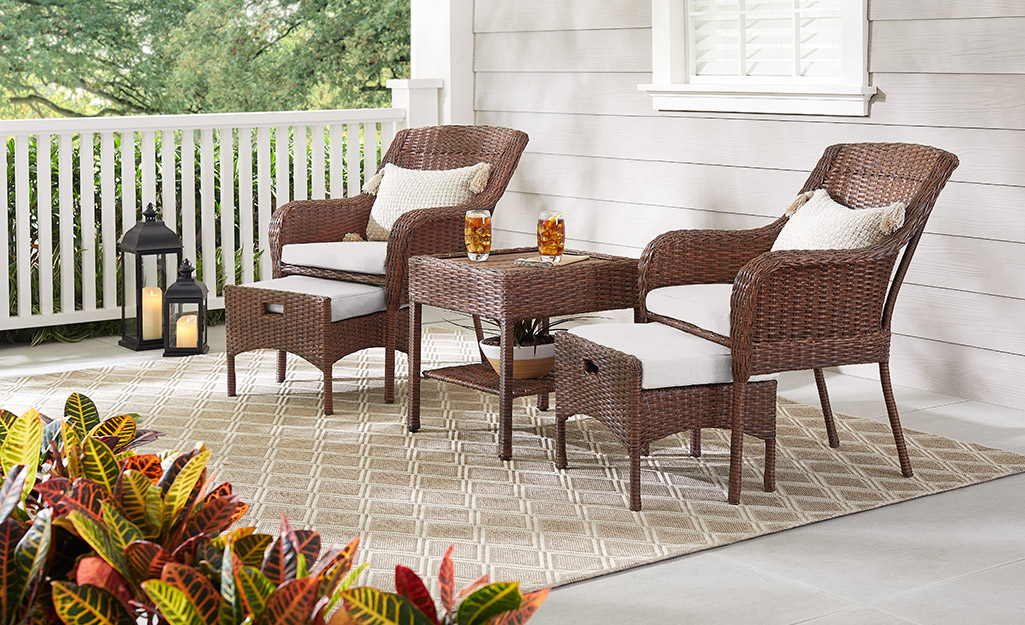 Wicker furniture and an outdoor area rug on a back porch.