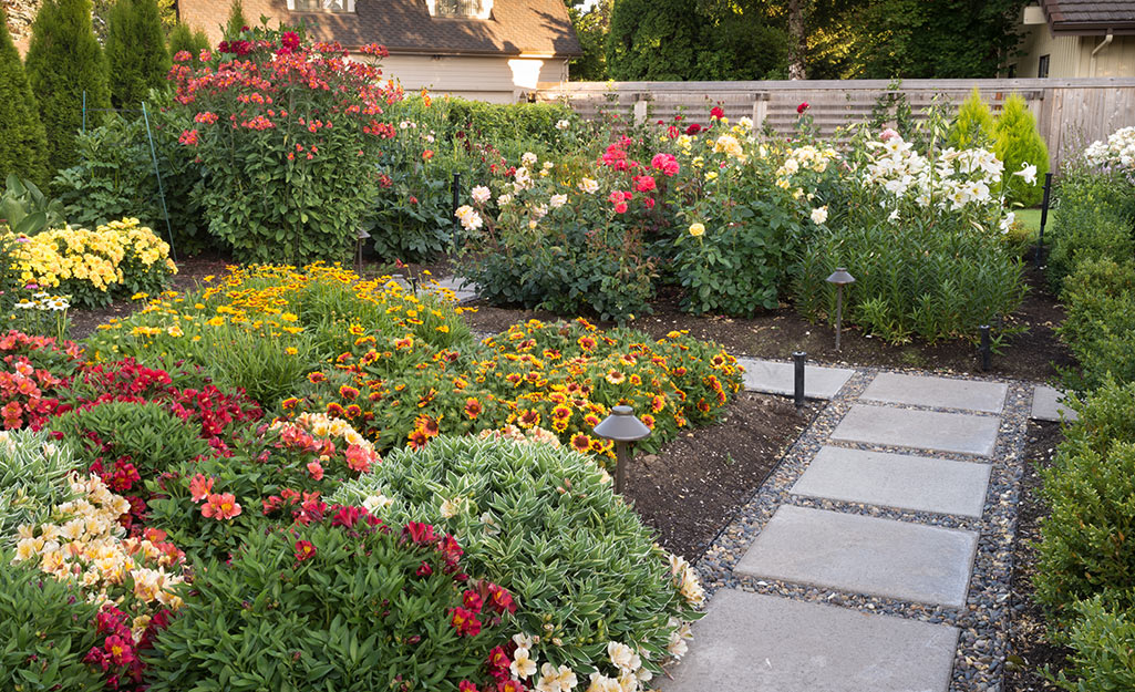 A gravel and paver garden path surrounded by flowering bushes.