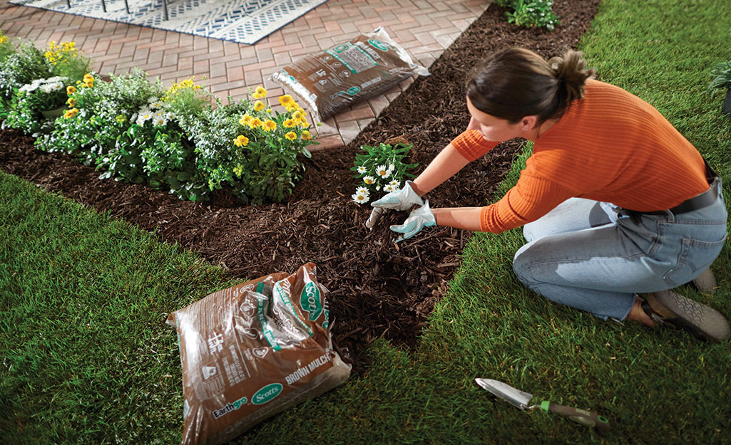 A woman laying fresh mulch in a garden bed.