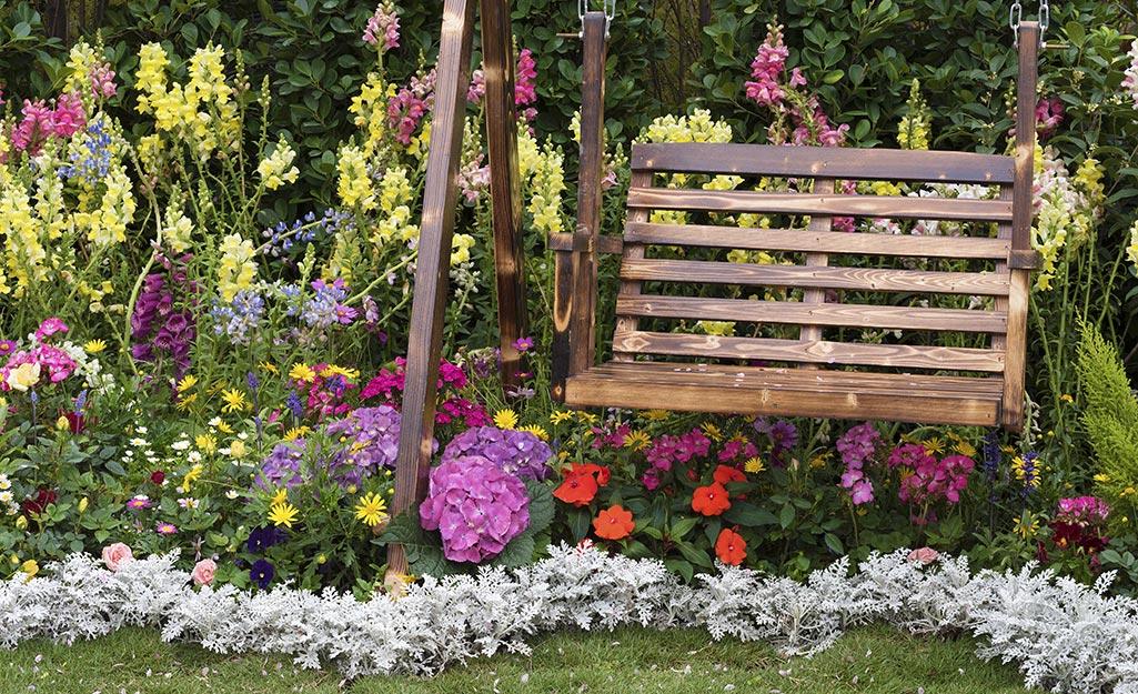 A flower border around a wooden swing.