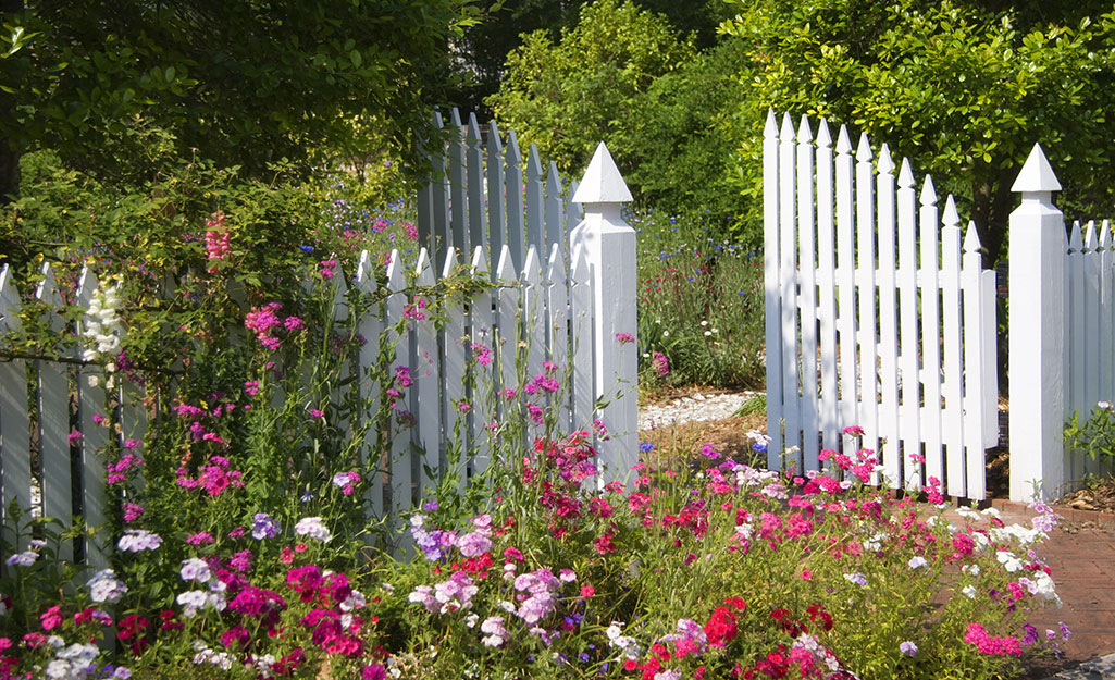 A white fence surrounded by flower gardens.
