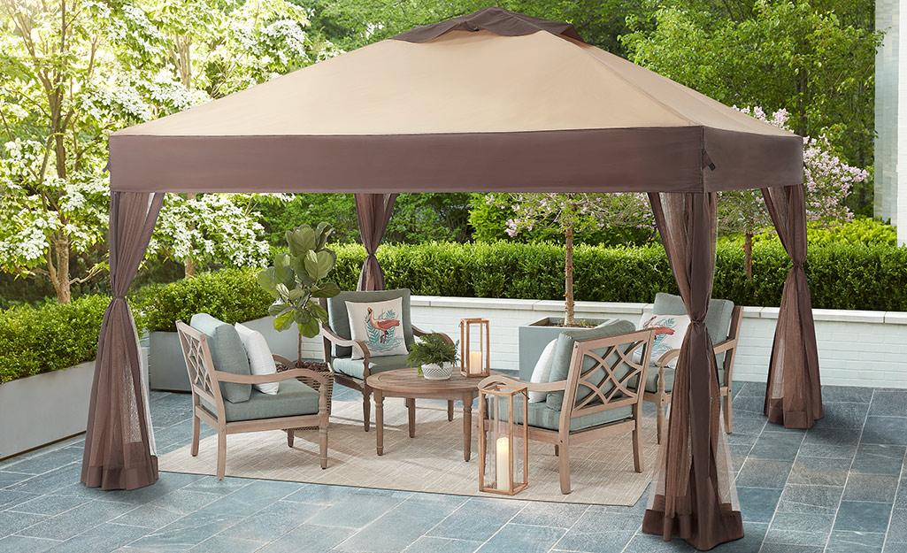 A pergola with tan drapes and patio furniture.