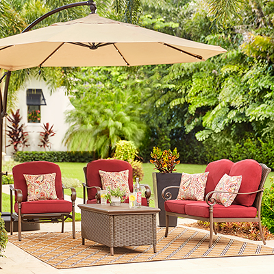 a small backyard patio featuring a loveseat, umbrella and outdoor coffee table
