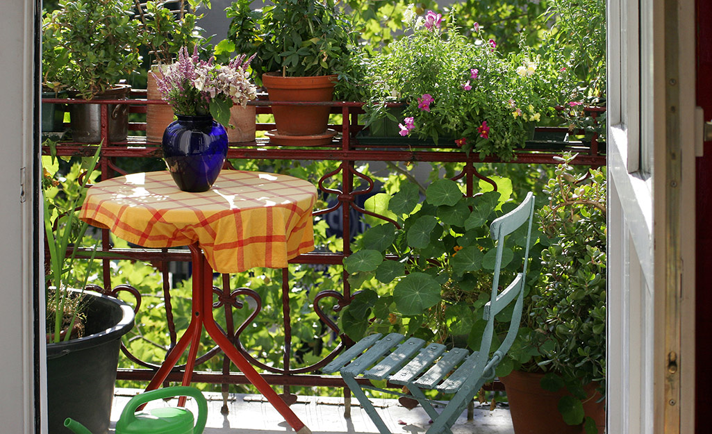 A balcony patio featuring plants and a bistro set.