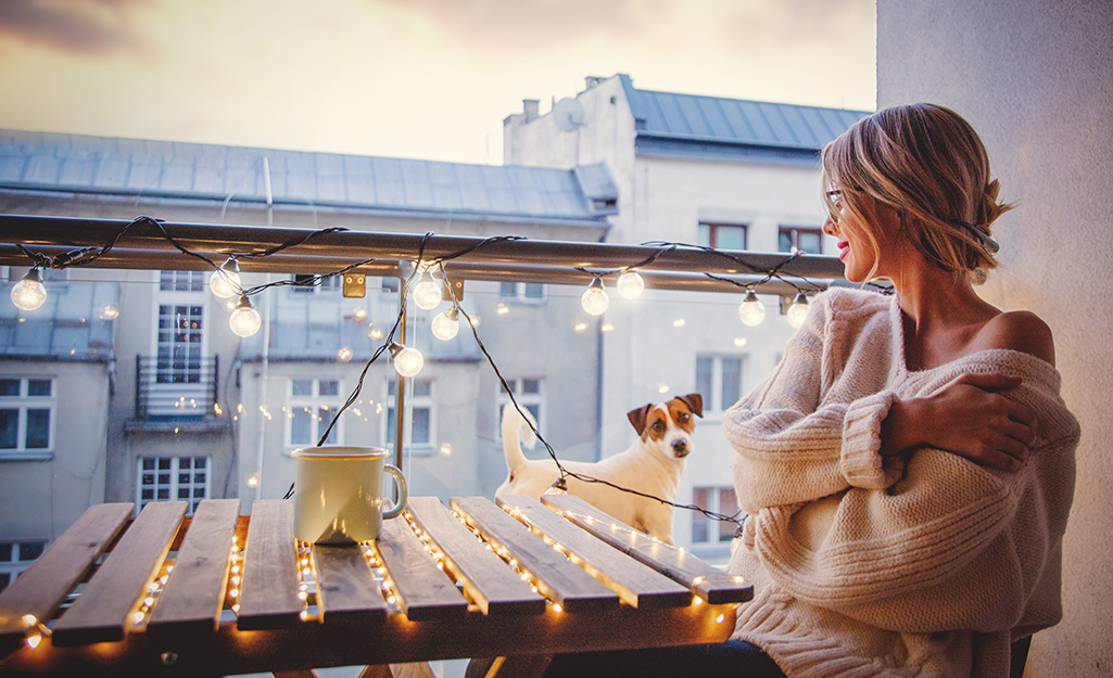 Woman admiring her lighted patio table and balcony lights.