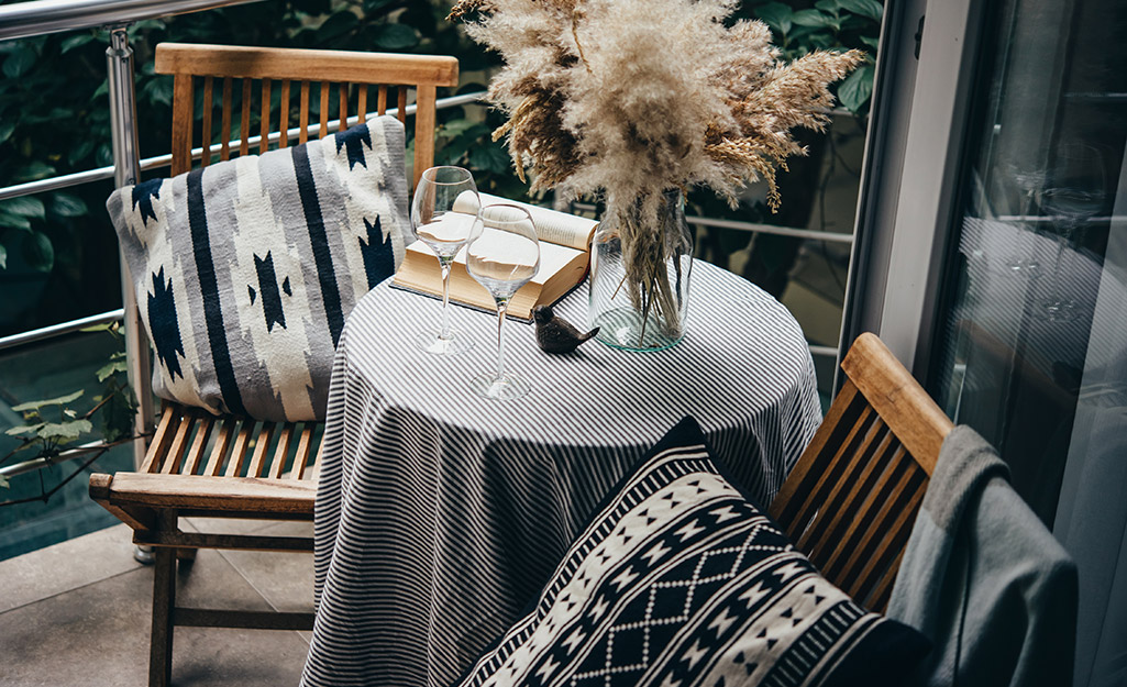 Round table covered in gray print tablecloth with complementary pillows on balcony.