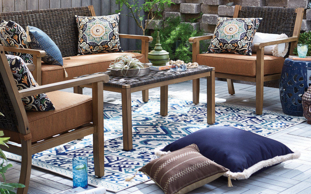 a balcony patio featuring furniture, accent pillows and an outdoor rug