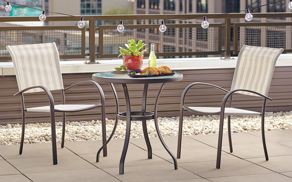 a balcony patio featuring a bistro set and string lights
