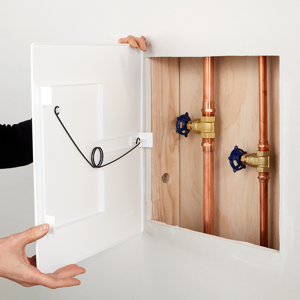 An open wall panel reveals gate valves on copper pipe.