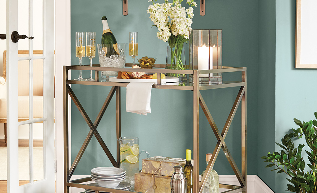 A bar cart with glass vases for flowers and candles.