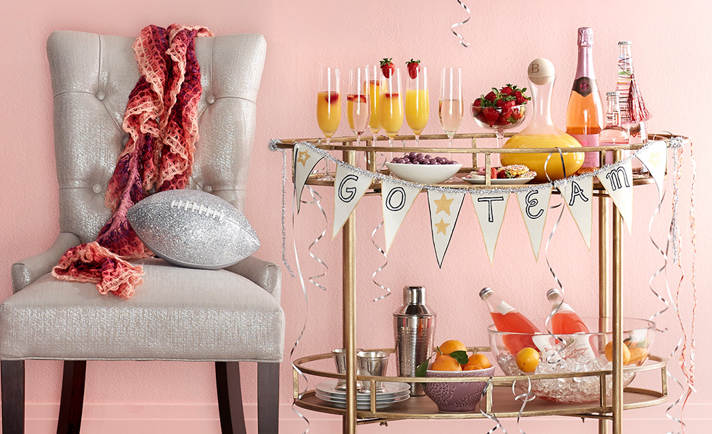 A festive banner decorates a bar cart for game day,.