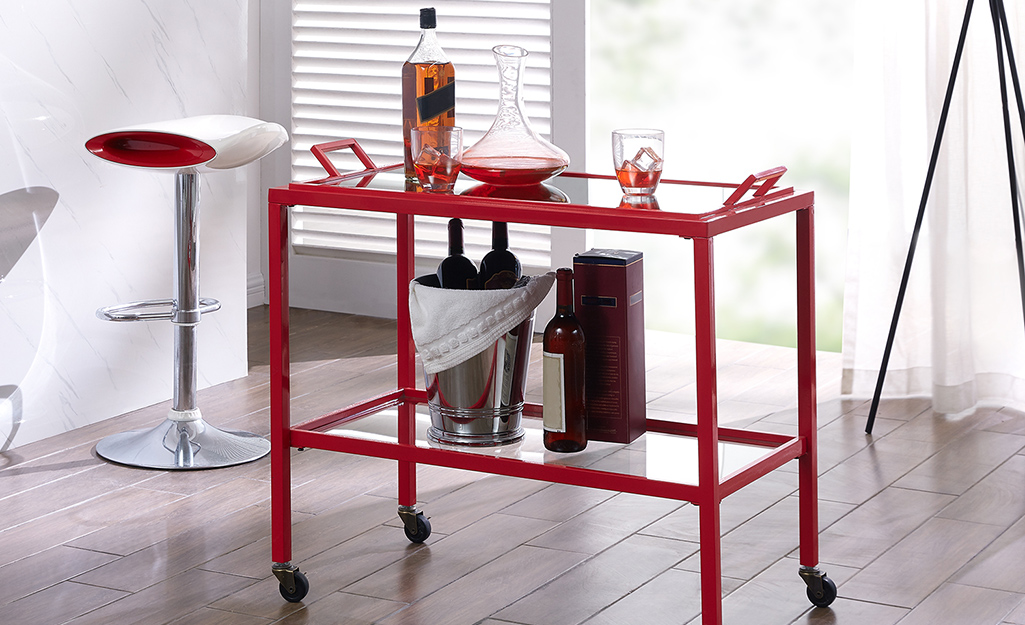 A bar cart has a modern look with the sharp lines of a red metal frame.