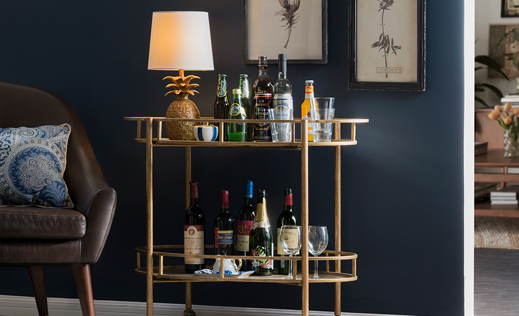 A gold bar cart with a small pineapple lamp on its shelf.