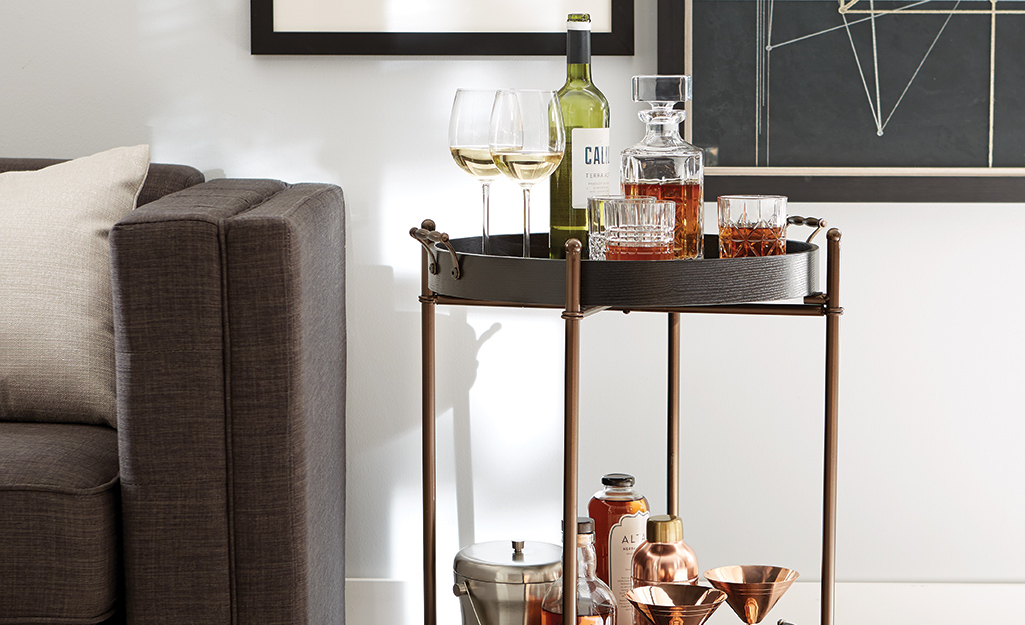 A bar cart with bar accessories including an ice bucket, shaker and decanter.