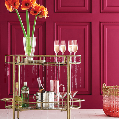 A gold-toned bar cart decorated with a vase of long-stemmed flowers.