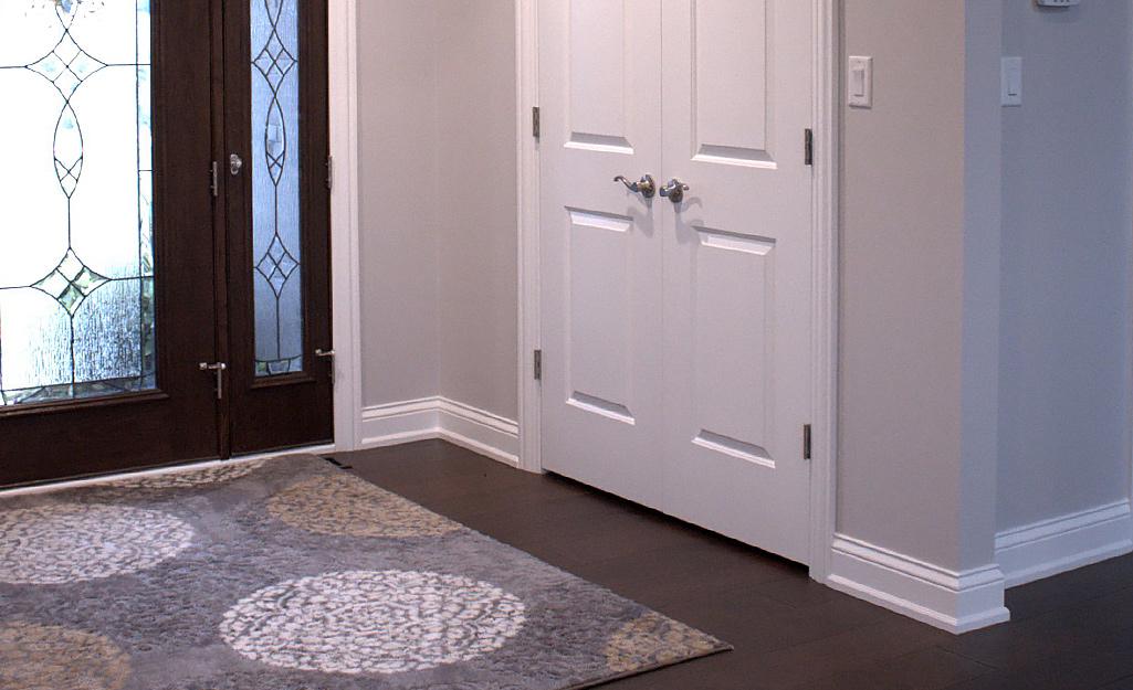 Một tấm ván chân tường truyền thống được sơn màu trắng để bổ sung cho bức tường màu xám.